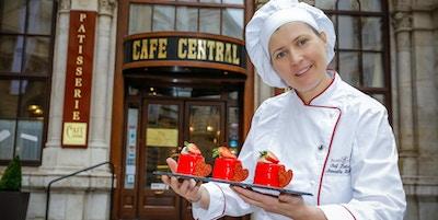 Café Central med en ansatt som holder kaker.